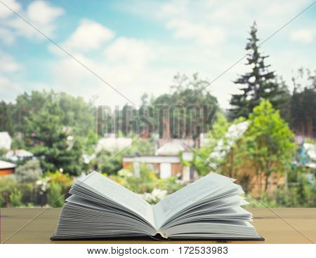 book wooden table with nature countryside blurred background