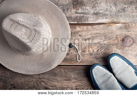 Men's casual accessories hat and shoes on old wooden background. Hipster outfit. Cowboy hat on grunge background. Top view