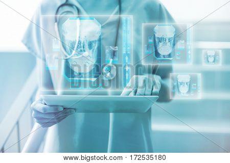 Digitally generated image of human skull against female surgeon using digital tablet 3d