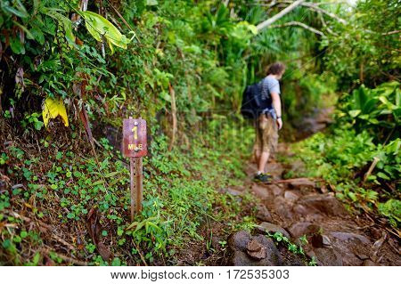 Young Male Tourist Hiking On The Famous Kalalau Trail Along Na Pali Coast Of The Island Of Kauai