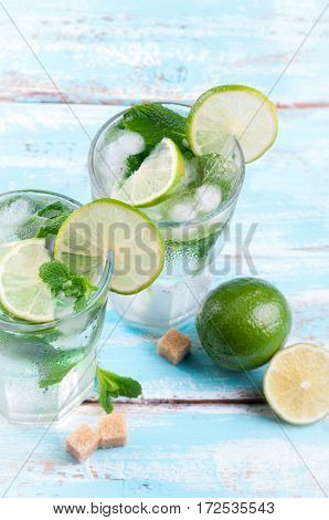 Mojito lime cocktail in bar on blue wooden backgroung. Ingredients for making mojito. Summer refreshing drink