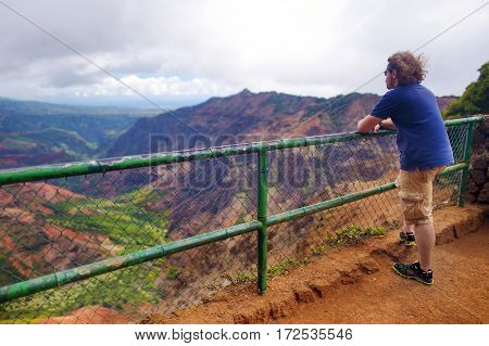 Young Male Tourist Enjoying The View Into Waimea Canyon, Kauai, Hawaii
