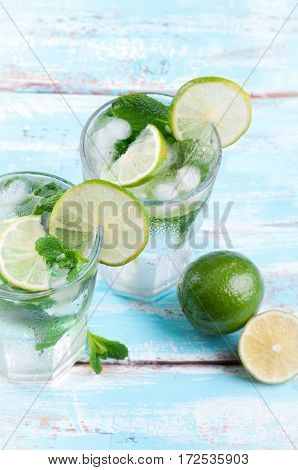 Mojito lime cocktail in bar on rustic wooden backgroung. Ingredients for making mojito. Summer refreshing drink