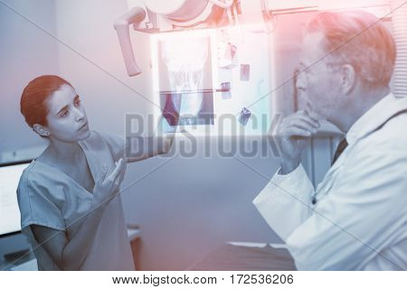Overhead of a x-ray of a human skull against nurse interacting with doctor in x-ray room