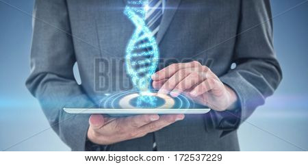 Businessman using digital tablet against digitally generated image of illuminated volume knob with dna strand