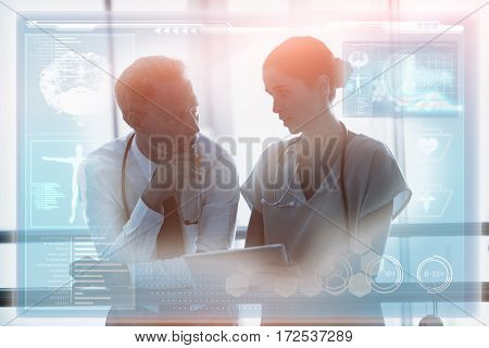 Medical biology interface in blue against doctor and colleague discussing over digital tablet 3d