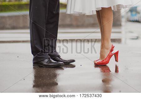 Feet in footwear of groom and the bride