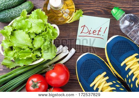 Healthy diet food and sport concept. Sport shoes water bottle note diet and fresh organic vegetables - lettuce cucumber tomatoes onions on wooden background. Top view