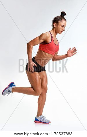 Healthy young fit woman running on white background