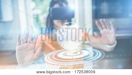 Digitally generated image of earth with light trail against beautiful woman using virtual reality headset in kitchen 3d