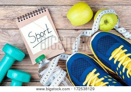 Sport shoes apples bottle of water measuring tape dumbbells and words