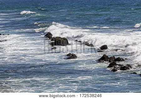 White waves and blue ocean washing over rocks at sea shore