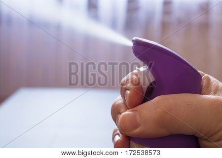 Men's hand holding air freshener bottle and spraying. Purple air freshener.