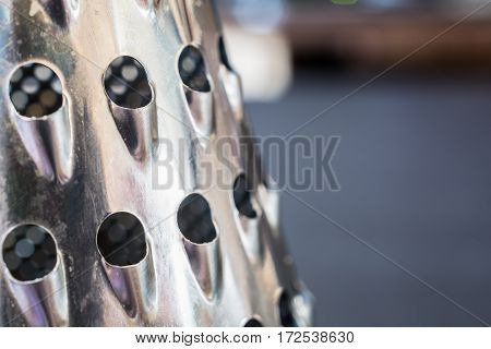 Close-up Photo of a Stainless Steel Metal Grater. Part of Item and Blurred Background.