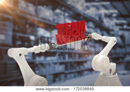 Metallic robotic hand holding team work text over white background against warehouse isle
