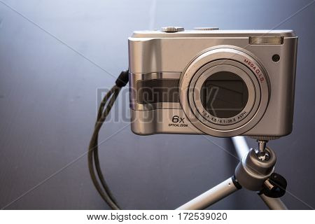 Silver compact digital photo camera. Front view.