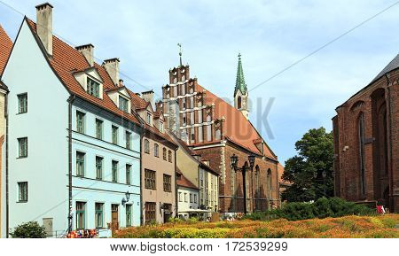 RIGA/ LATVIA - JULY 25, 2015: Old houses on the street Skarnu at the foot of St. Peter's Church. Riga Latvia.