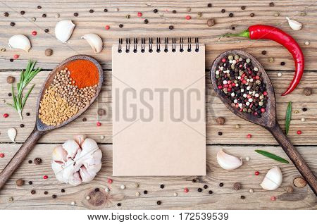 Spices background with copy space. Open blank notebook rosemary pepper paprika fenugreek coriander chilli and garlic on wooden background. Top view
