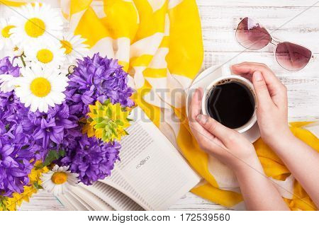 Woman's hands keep cup of coffee. Book bouquet of flowers female accessories - sunglasses and neckerchief on wooden table. Coffee break. Summer rest concept background. Top view