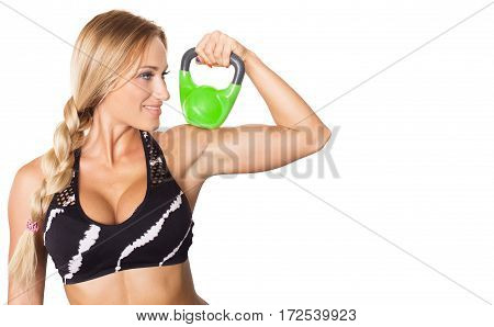 Young sexy fitness model holding green kettlebell isolated on white