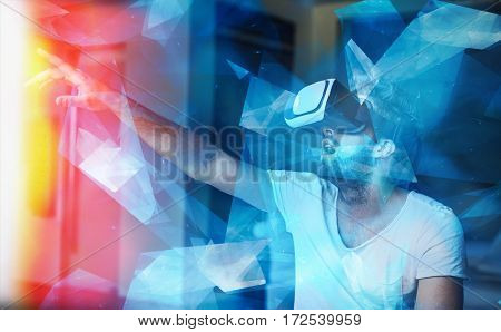 Young man with VR glasses playing virtual reality touching orange light source with polygons