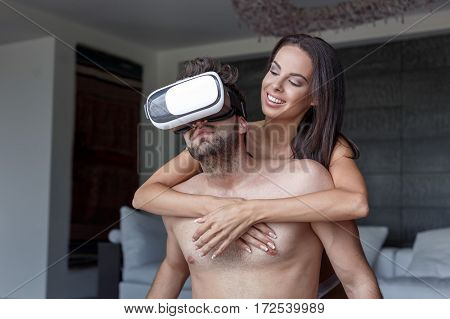 Young naked couple using VR headset virtual reality indoor