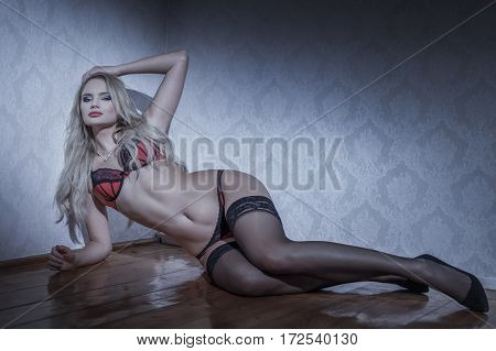 Sensual blonde woman in underwear laying on floor at night