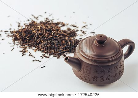 Yixing teapot and black Chinese tea on a white background