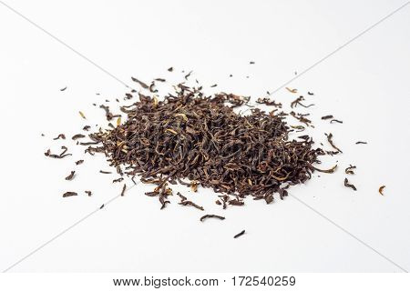 Dried black Chinese tea leaves on white background