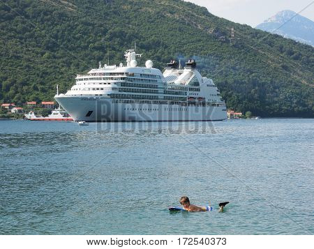 Bay of Kotor Montenegro - 24 June 2014: Boy swimming in front of a cruiseship on the bay of Kotor Montenegro