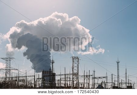 Clouds of thick smoke NPP Nuclear Power Plant in rays of bright sunlight