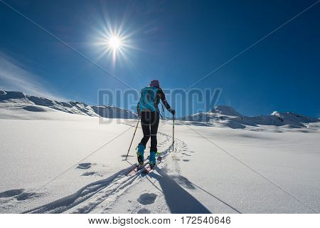 uphill girl with seal skins and ski mountaineering on the alps