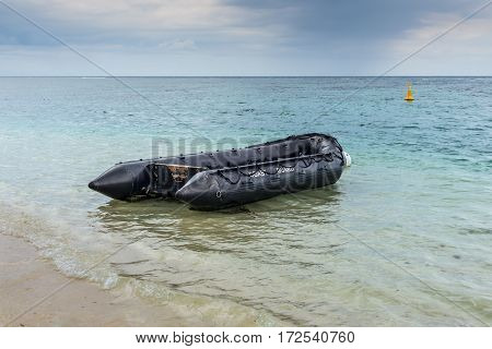 Flic en Flac Mauritius - December 9 2015: Coastguard's dinghy on the shores of the Indian ocean on a cloudy day in Flic en Flac bay Mauritius.