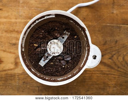Freshly ground coffee in electric coffee grinder.