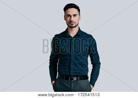 Confidence and charisma. Good looking young man keeping hands in pockets and looking at camera while standing against grey background