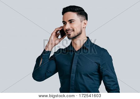 Pleasant business talk. Good looking young man talking on smart phone and looking away while standing against grey background