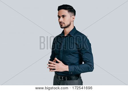 Thinking about solutions. Handsome young man holding hands clasped and looking away while standing against grey background