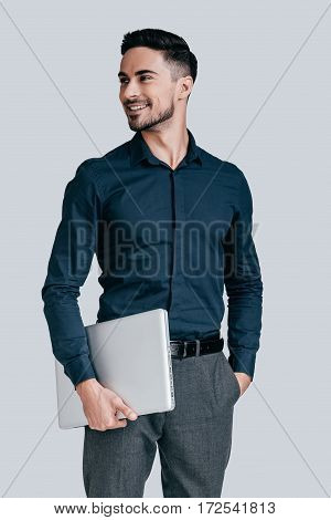 Successful and handsome. Good looking young man in shirt carrying laptop and looking away with smile while standing against grey background