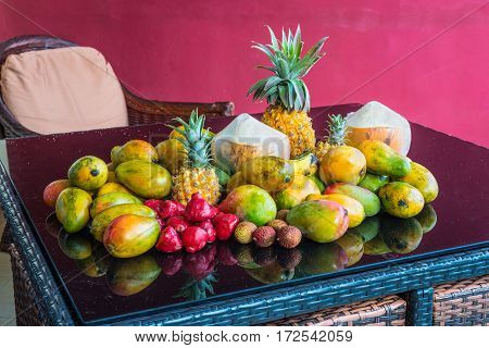 Fresh tropical Mauritius fruits on a purple glass table in the magenta background. The selection includes Coconut Rose Apple Mango and Pineapples.