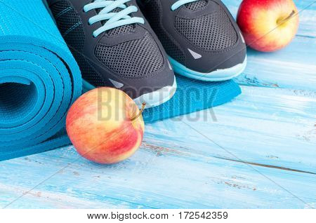 Sport equipment and sneakers. Yoga mat sport shoes and apples on blue wooden background. Concept healthy lifestyle healthy food sport and diet. Copy space