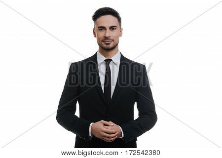 Confidence and charisma. Handsome young man in full suit holding hands clasped and looking at camera while standing against white background