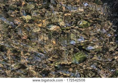 Natural colorful stones on a lake bottom outdoors.