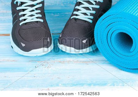 Sport equipment and sneakers. Yoga mat and sport shoes on blue wooden background. Concept healthy lifestyle healthy food sport and diet. Copy space