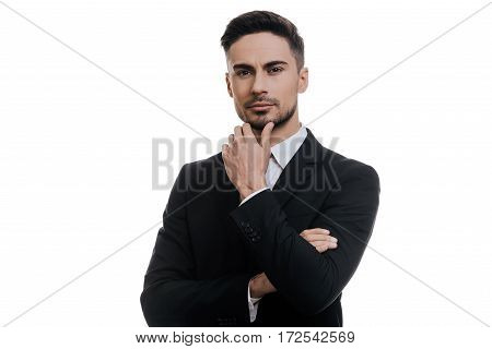 Thoughtful man. Handsome young man in full suit holding hand on chin and looking at camera while standing against white background