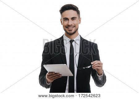 Confident advisor. Handsome young man in full suit holding digital tablet and smiling while standing against white background