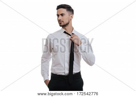 Feeling tired. Exhausted young man in formalwear looking away and taking off his tie while standing against grey background