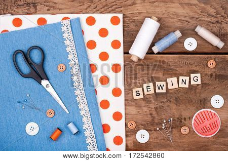 Jeans and cotton fabric for sewing lace and accessories for needlework on old wooden background. Spool of thread scissors buttons sewing supplies. Set for needlework top view. Handmade background