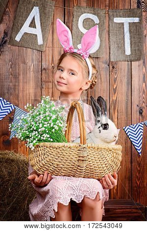Easter holidays. Happy little child girl holds Easter Bunny and painted eggs and smiling.