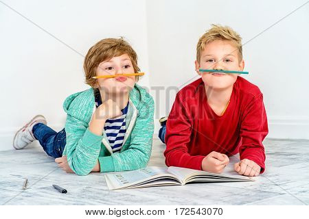 Joyful laughing children reading a book together. Children's fashion. Education. Happiness, activity and child concept. Copy space.