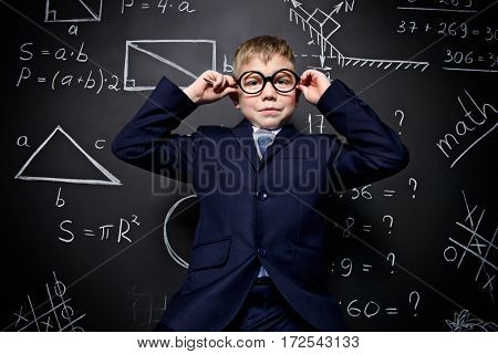 Smart schoolboy in black suit and glasses over school blackboard. Educational concept.